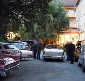 Hotellets baksida med parkering. Längst till vänster aktern på en 1959 Pontiac, därefter en modern svensson-bil och till höger om den en 1963 Buick. Bilen som är omgiven av människor är en 1958 Oldsmobile.