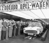 Det är den 9 november 1956 och den förgyllda 2-miljonte Opeln hyllas översvallande av fabrikens manliga direktörer och fabriksarbettare!
