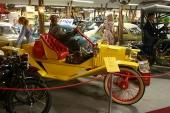 Ett myller av bilar, välklädda skyltdockor och annan automobilia. I förgrunden en knallgul 1912 Ford Model T Speedster med röd läderklädsel.