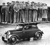 """Fabriksreklam med texten: """"DKW-karossen är så stabil, att den tål den enorma belastningen av 32 fullvuxna män utan att dörrarna klämmas fast eller fönsterrutorna spricka. Efter denna fotografering vid fabriken levererades vagnen utan minsta justering eller reparation"""". Den här bilden är en klassiker och användes flitigt under 30-talet."""