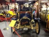 Vilken lyx med mörkblå lackering och matchande beige randning, toppat med massvis av glänsande mässing! Bilen är en 1910 Buick Roadster. Till vänster syns fronten på 1912 Ford Model T Speedster.