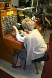 Den här damen måste oupphörligt passa telefonväxeln! Så till den milda grad att hon äter äpple och dricker kaffe på arbetsplatsen. Det kommer många samtal, telefonväxeln på Motala Motormuseum är nästan ständigt upptagen!